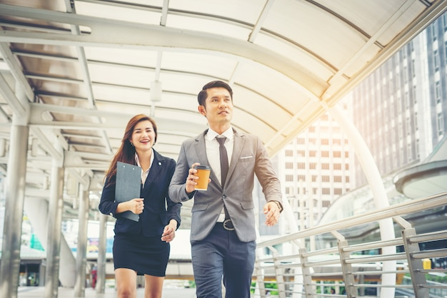 Pessoas de negócios caminhando pelo escritório da passagem. sorrindo um para o outro.