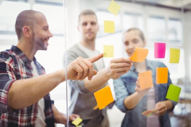 Pessoas de negócios, colando notas adesivas no escritório