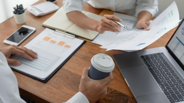 Pessoas de negócios conversando discutindo com o colega de trabalho, analisando tabelas e gráficos de dados de documentos financeiros