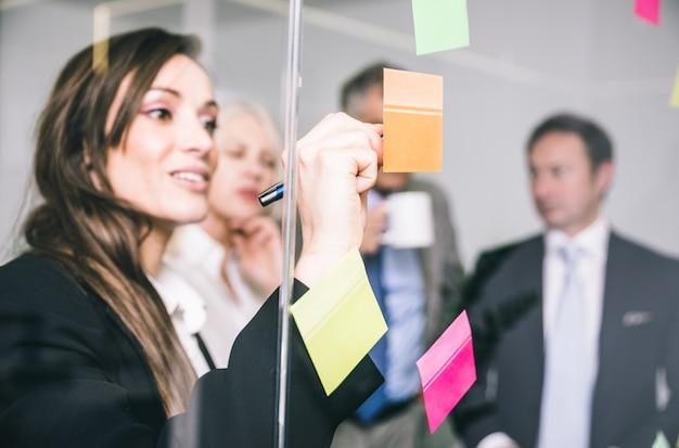 Pessoas de negócios, conversando e escrevendo notas no post
