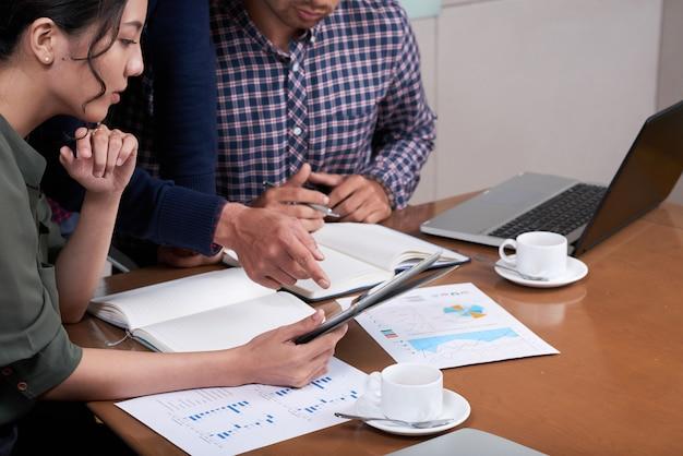 Pessoas de negócios cortadas discutindo gráficos e diagramas no escritório