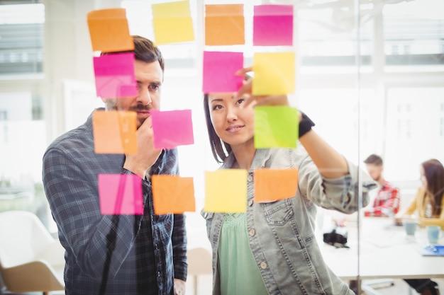 Pessoas de negócios criativos olhando multi colorido notas auto-adesivas em vidro