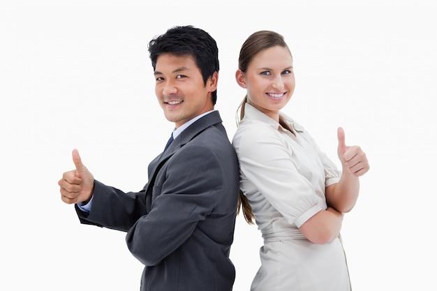 Pessoas de negócios de pé para trás com o polegar para cima