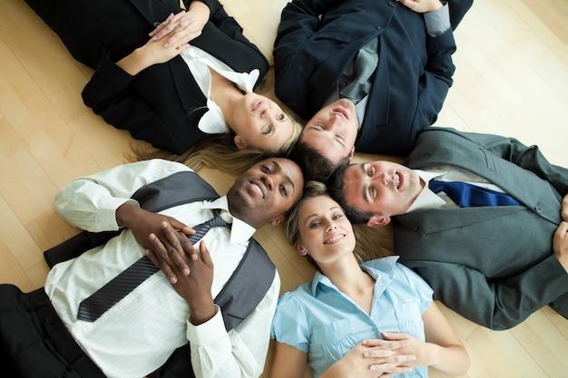 Pessoas de negócios deitados em um círculo no chão