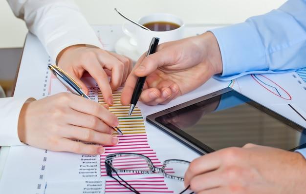 Pessoas de negócios, discutindo as tabelas e gráficos mostrando os resultados de seu trabalho em equipe bem-sucedido.