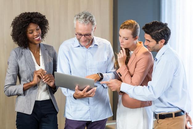 Pessoas de negócios discutindo sobre laptop a sorrir
