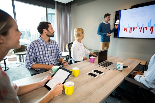 Pessoas de negócios, discutindo sobre o gráfico durante uma reunião