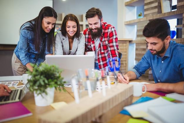 Pessoas de negócios, discutindo sobre o laptop na mesa
