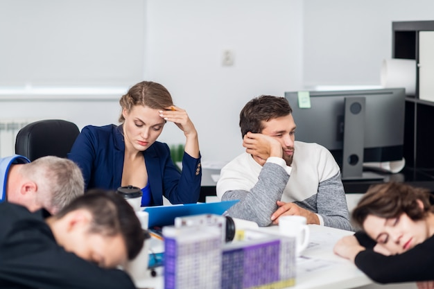 Pessoas de negócios, dormindo na sala de conferências durante uma reunião, concentre-se em uma mulher
