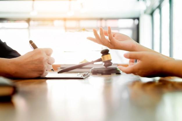 Pessoas de negócios e advogados discutindo documentos de contrato sentados à mesa