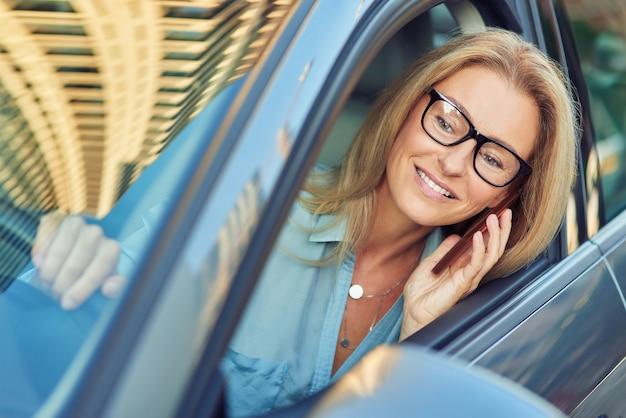 Pessoas de negócios e conceito de transporte sorrindo, mulher de negócios de meia-idade usando óculos