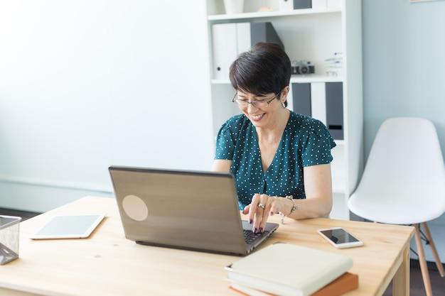 Pessoas de negócios e o conceito de tecnologia - mulher de meia idade está trabalhando no escritório com o laptop.