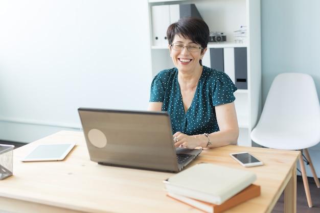 Pessoas de negócios e o conceito de tecnologia - mulher de meia-idade trabalhando em um laptop