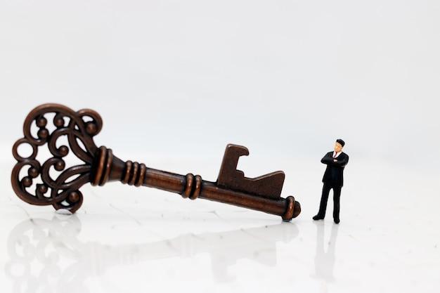 Pessoas de negócios em miniatura com a chave do sucesso