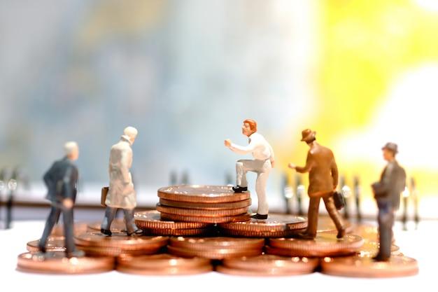Pessoas de negócios em miniatura em pé no degrau do dinheiro da moeda. finança .