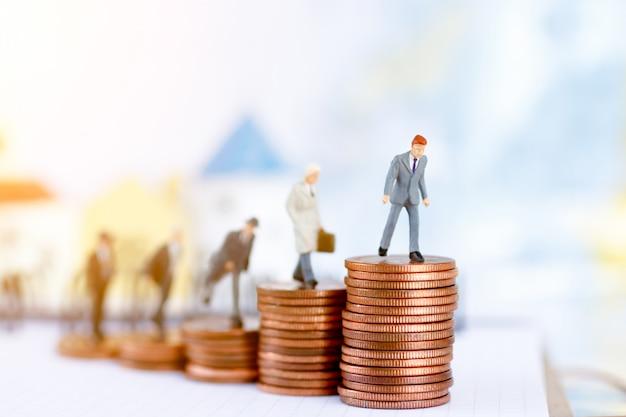 Pessoas de negócios em miniatura em pé no degrau do dinheiro da moeda