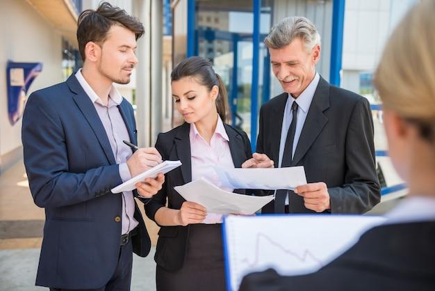 Pessoas de negócios em ternos discutindo a estratégia de negócios.