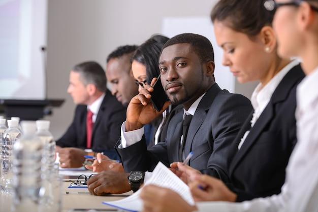 Pessoas de negócios em trajes formais discutindo algo.