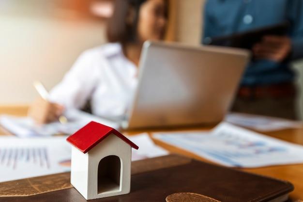 Pessoas de negócios estão discutindo sobre o modelo de casa de projeto imobiliário