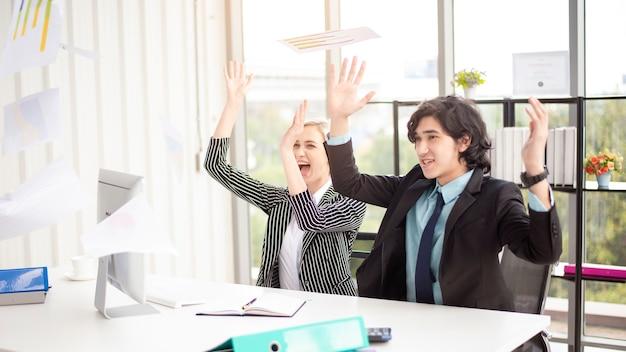 Pessoas de negócios estão felizes com o sucesso comercial no escritório