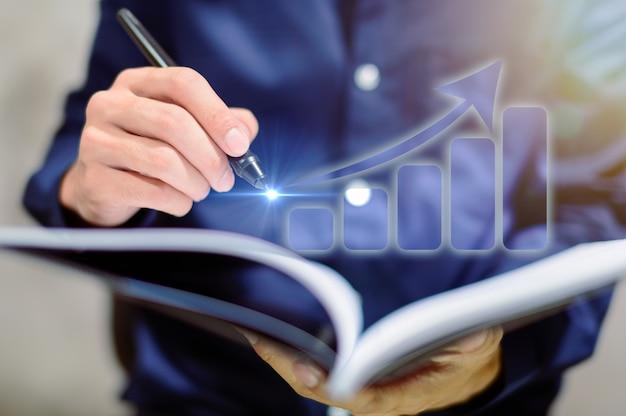 Pessoas de negócios exibem tabelas gráficas em cadernos
