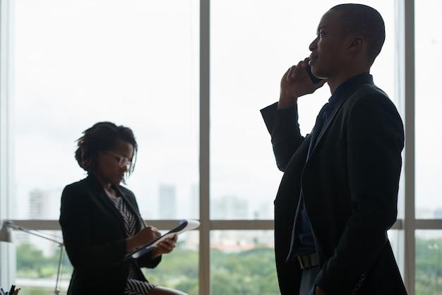 Pessoas de negócios, falando no telefone e escrevendo no caderno contra a janela do escritório
