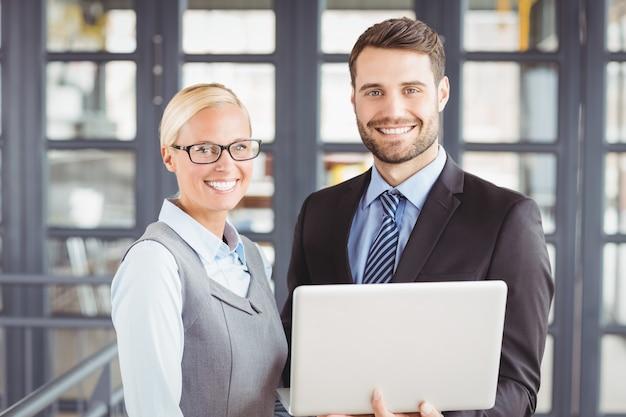 Pessoas de negócios feliz com laptop em pé no escritório