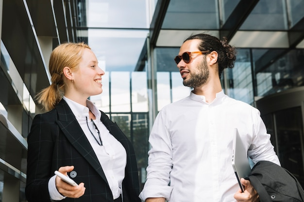Pessoas de negócios feliz em pé fora do escritório olhando uns aos outros