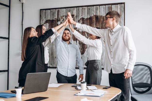 Pessoas de negócios feliz mostrando trabalho em equipe e dando cinco depois de assinar um acordo ou contrato com os parceiros no interior do escritório. pessoas felizes sorrindo. acordo ou conceito de contrato. - imagem