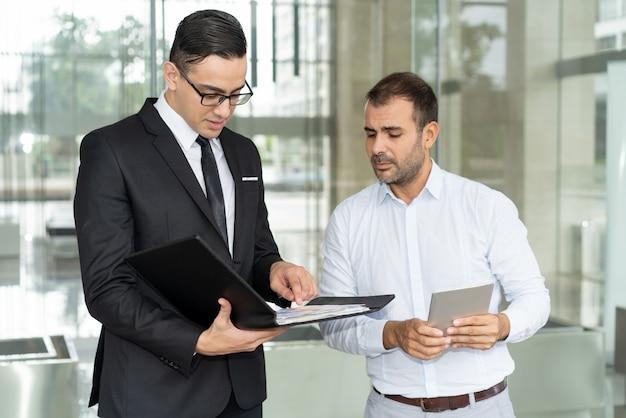 Pessoas de negócios infelizes lendo relatório financeiro anual