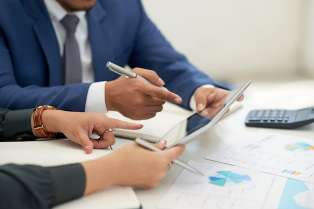 Pessoas de negócios irreconhecíveis, sentado na reunião com gráficos, olhando e apontando para tablet