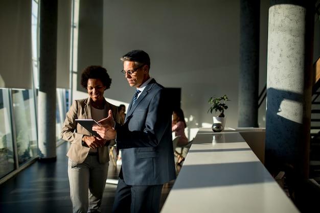 Pessoas de negócios multiétnico usando tablet digital em pé no escritório