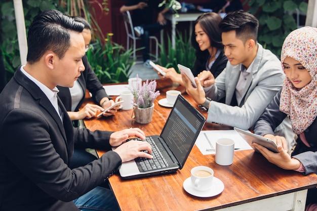 Pessoas de negócios ocupadas trabalhando com a equipe em um café