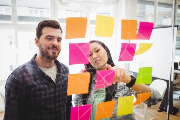 Pessoas de negócios olhando multi colorido notas auto-adesivas em vidro