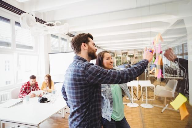 Pessoas de negócios olhando notas autoadesivas no vidro a sorrir