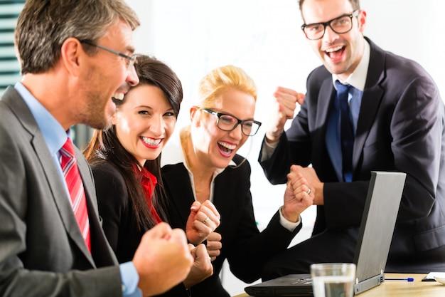 Pessoas de negócios olhando para laptop com sucesso