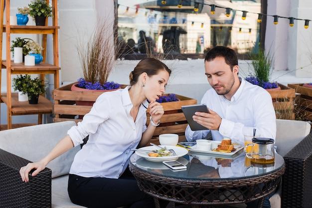 Pessoas de negócios olhando tablet digital no café durante uma reunião