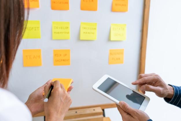 Pessoas de negócios organizando notas autoadesivas comentando e debatendo sobre o colega de prioridades de trabalho em um espaço de trabalho moderno.