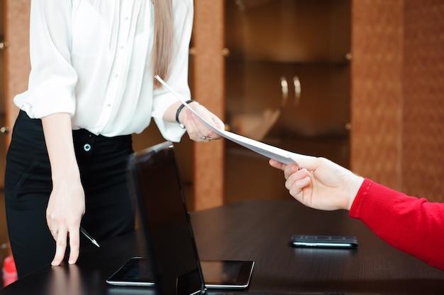 Pessoas de negócios, passando o documento para o gerente dela