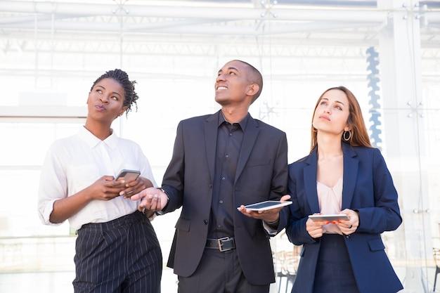 Pessoas de negócios pensativo animado com gadgets digitais