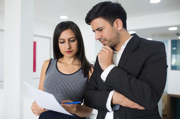 Pessoas de negócios pensativo grave analisando documento juntos