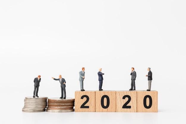 Pessoas de negócios permanente no número do bloco de madeira 2020