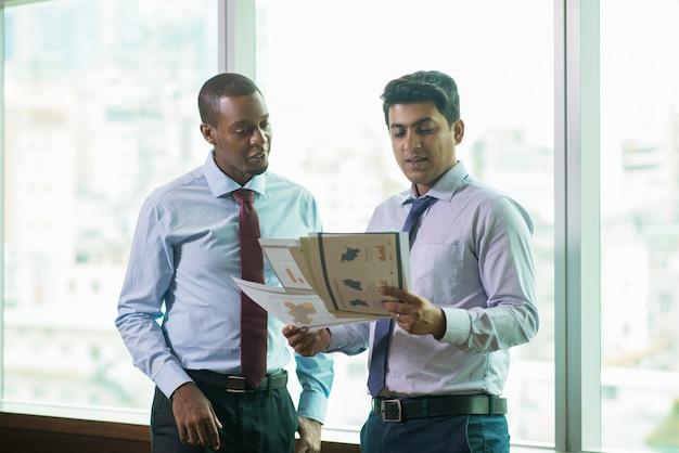 Pessoas de negócios positivos, analisando documentos com dados financeiros