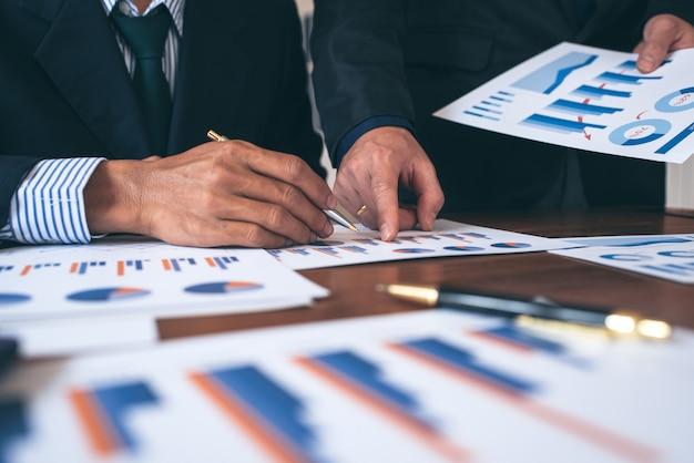 Pessoas de negócios que discutem gráficos e tabelas mostrando os resultados de dados e informações bem-sucedidos do trabalho em equipe.