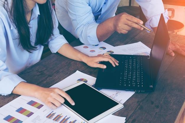 Pessoas de negócios que estão fazendo um brainstorming na mesa do escritório, estão analisando os relatórios financeiros e o laptop da tela apontadora