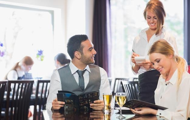 Pessoas de negócios que lêem o menu e solicitando