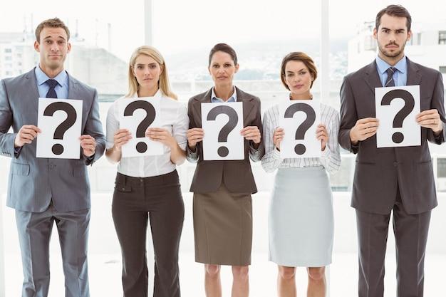 Pessoas de negócios que mantêm sinais de ponto de interrogação