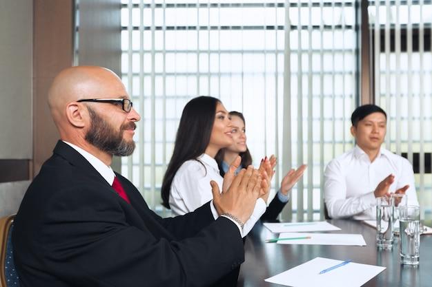 Pessoas de negócios, reunidos em torno de uma mesa da sala de reuniões, discutindo a estratégia