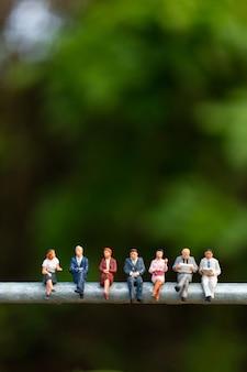 Pessoas de negócios, sentado em um fio