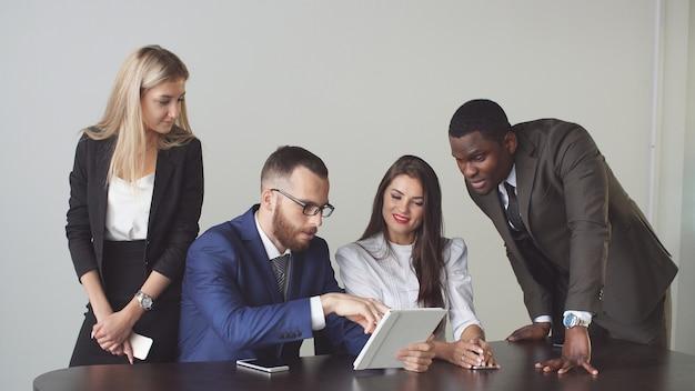 Pessoas de negócios, sentar e ter reunião informal olhando juntos para dados no tablet digital.